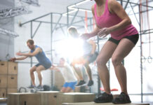 People doing box jump exercise in crossfit gym in South Bend